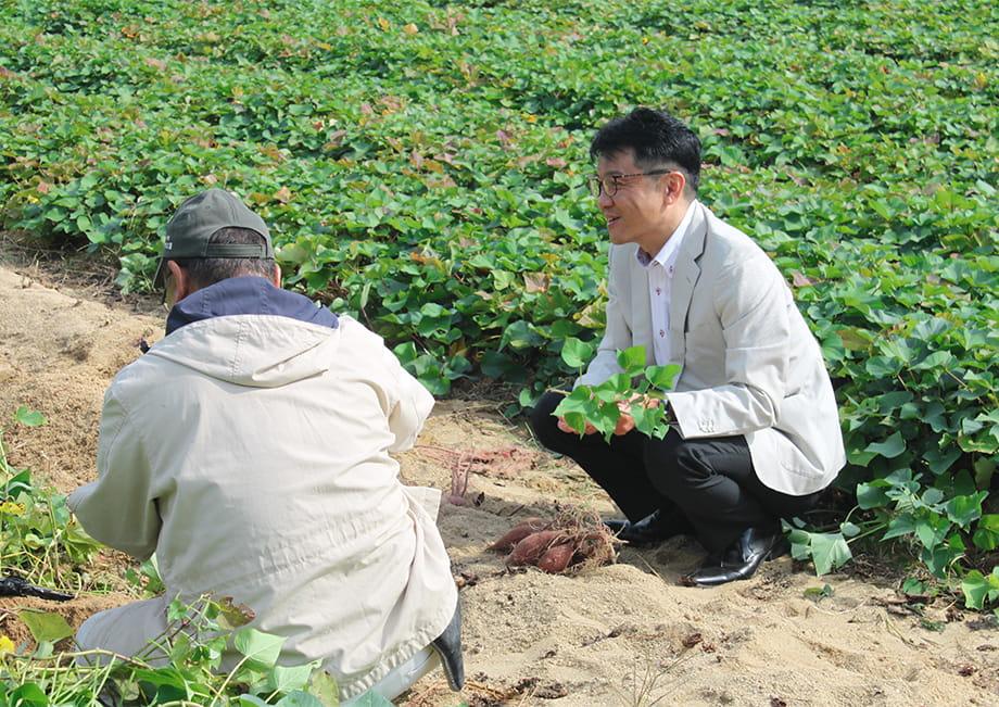 畑にて農家さんとコミュニケーションをはかる、なかや宗義代表
