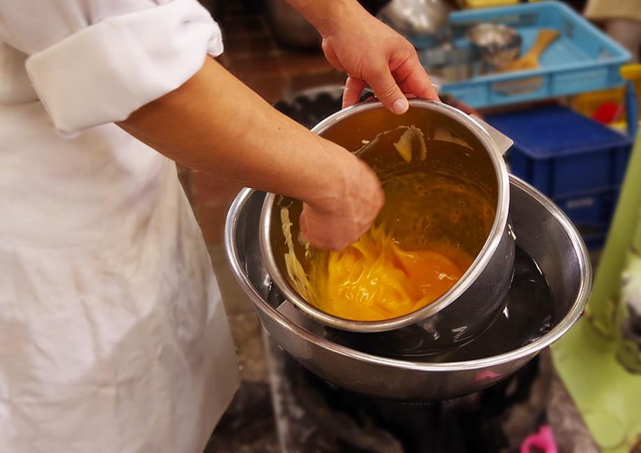 湯銭をしながら卵黄と砂糖を混ぜている職人