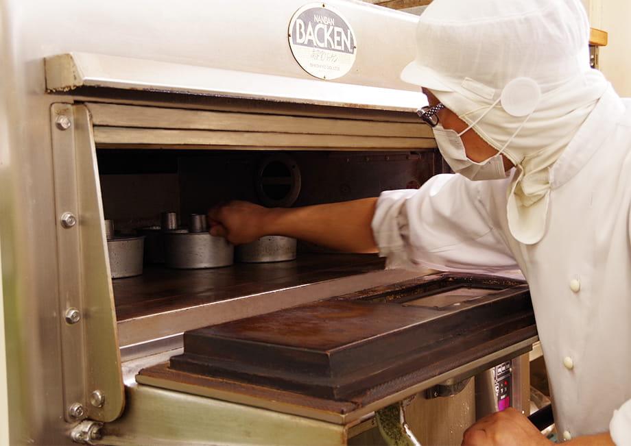 オーブンの中に、シフォンケーキの生地が入った容器を並べる職人