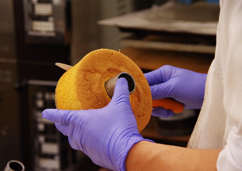 ナイフでシフォンケーキの形を整えている職人
